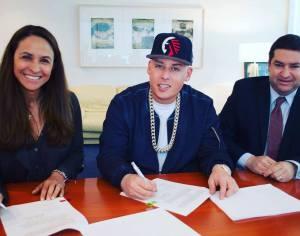 Cosculluela (centro) firmando el acuerdo con Warner Music Latin (Foto tomada de su Facebook Oficial)
